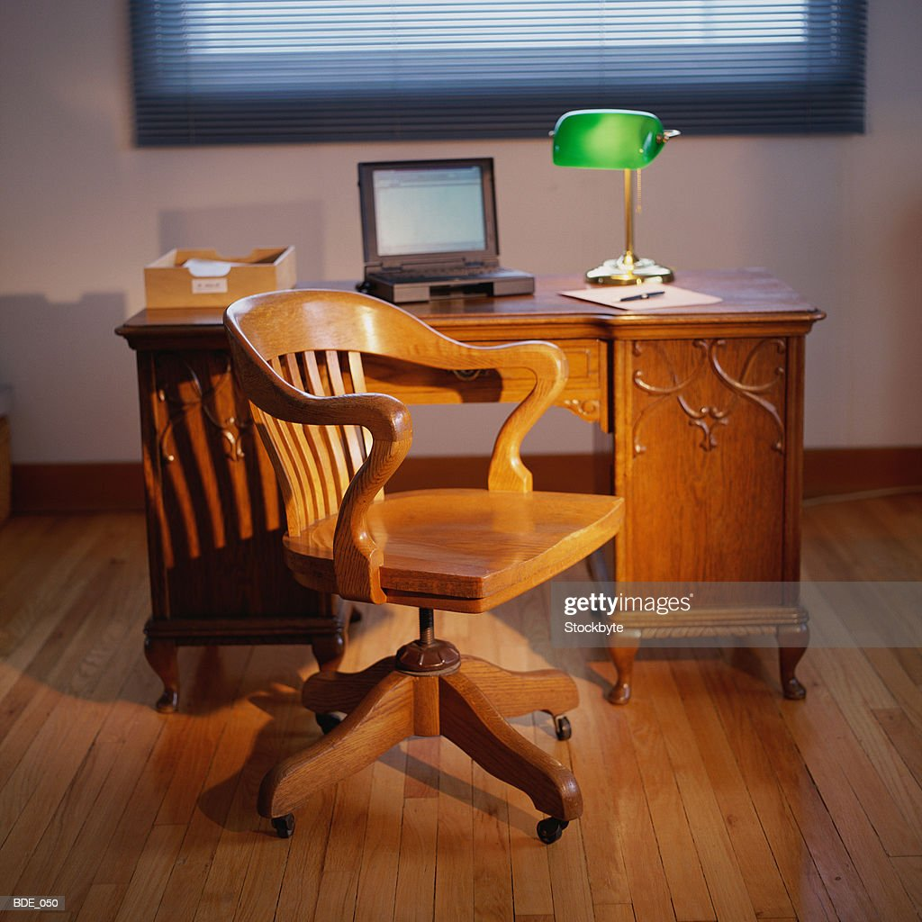 Home office with desk bankers lamp laptop computer and chair stock photo