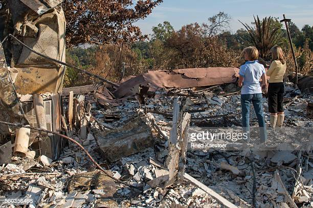 home owner and friend look over the ruins of a house fire - ruined stock pictures, royalty-free photos & images