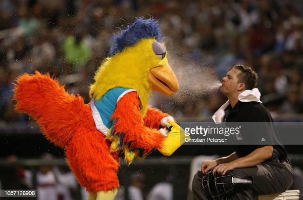 Home plate umpire Adam Beck spits water onto the San Diego Chicken mascot during a break from the Arizona Fall League All Star Game at Surprise...