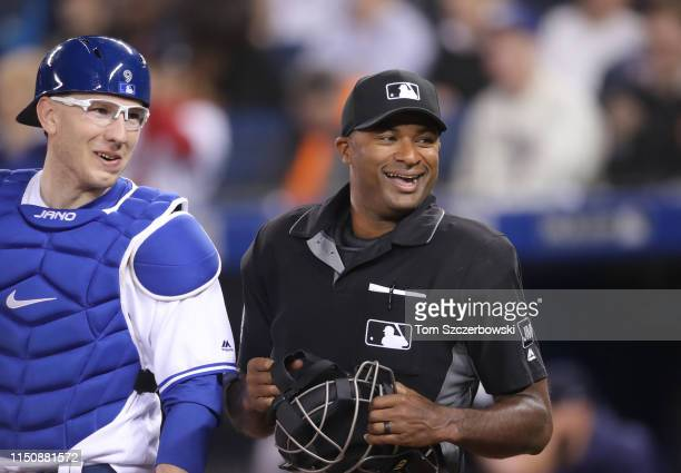 Home plate umpire Alan Porter and Danny Jansen of the Toronto Blue Jays laugh as they look to the Blue Jays dugout shortly before the start of MLB...
