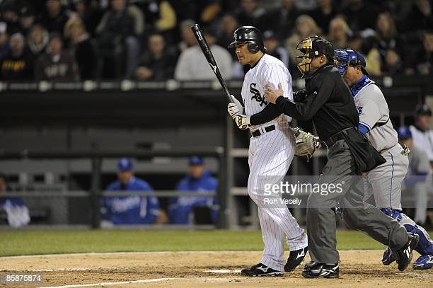 Home plate umpire Bill Hohn restrains Carlos Quentin of the Chicago White Sox after Quentin was hit by a pitch thrown by Zach Greinke of the Kansas...