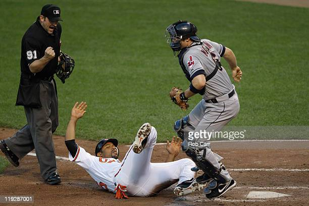 Home plate umpire Brian Knight calls out Derrek Lee of the Baltimore Orioles at home plate after catcher Lou Marson of the Cleveland Indians tagged...