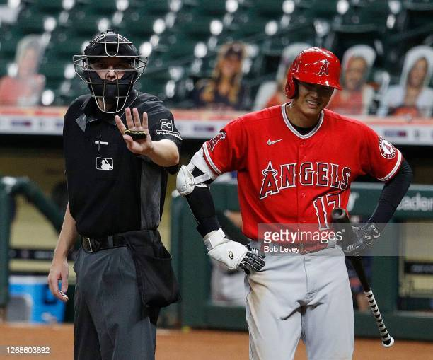 Home plate umpire Clint Vondrak motions to Los Angeles Angels manager Joe Maddon who expressed his dislike with the called strike three on Shohei...