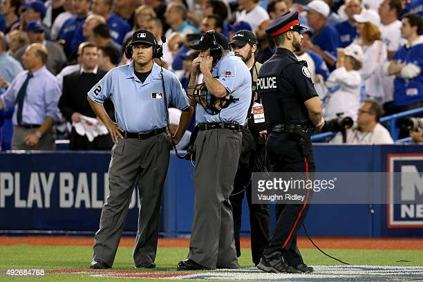 Home plate umpire Dale Scott calls in for a replay in the seventh inning in game five of the American League Division Series at Rogers Centre on...