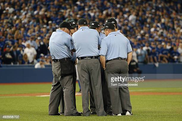Home plate umpire Dale Scott consults with fellow umpires during a video review before ruling that Rougned Odor of the Texas Rangers scored a run...