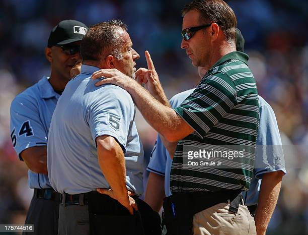 Home plate umpire Dale Scott is examined by trainer Rob Nodine of the Seattle Mariners after he was hit with a foul ball during the game against the...
