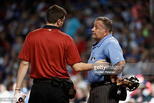 Home plate umpire Dale Scott is looked at by a Arizona Diamondbacks team trainer after being hit by a foul ball during the first inning of the MLB...
