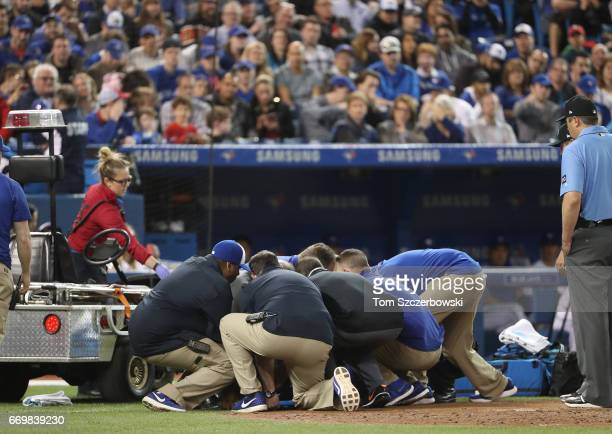 Home plate umpire Dale Scott is placed onto a stretcher and lifted onto a cart before coming out of the game after sustaingin an injury after he was...