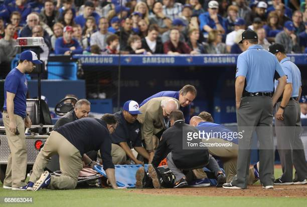 Home plate umpire Dale Scott is taken out of the game on a stretcher after being hit by a foul ball in the eighth inning of the Toronto Blue Jays MLB...