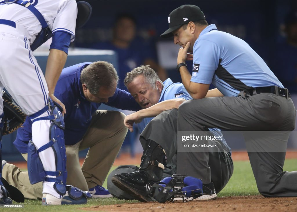 Home plate umpire Dale Scott #5 is tended to by a Toronto Blue Jays trainer as first base umpire Jim Reynolds #77 looks on after Scott took a foul ball in the eighth inning during MLB game action against the Baltimore Orioles at Rogers Centre on April 14, 2017 in Toronto, Canada.