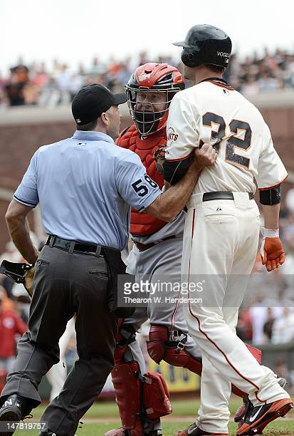 Home Plate umpire Dan Iassogna has to restrain pitcher Ryan Vogelsong of the San Francisco Giants from charging the mound after almost getting hit...