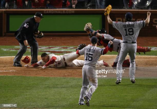 Home plate umpire Dana DeMuth calls Allen Craig of the St Louis Cardinals safe at home against Jarrod Saltalamacchia of the Boston Red Sox in the...