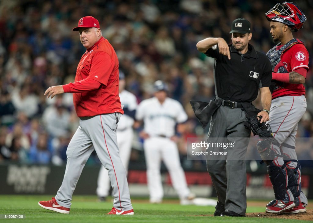 Home plate umpire David Rackley throws out Los Angeles Angels of Anaheim manager Mike Scioscia during the fourth inning of a game against the Seattle Mariners at Safeco Field on September 9, 2017 in Seattle, Washington.