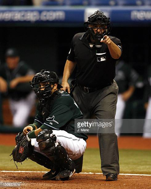 Home plate umpire Eric Cooper has some words with the Texas dugout as Tampa Bay catcher Dioner Navarro listens in during Wednesday night's action at...