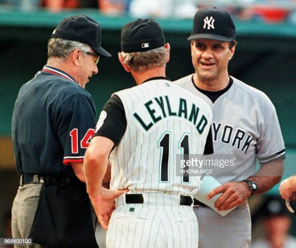 Home plate umpire Frank Pulli watches New York Yankees manager Joe Torre and Florida Marlins manager Jim Leyland meet at the plate 13 June at Pro...