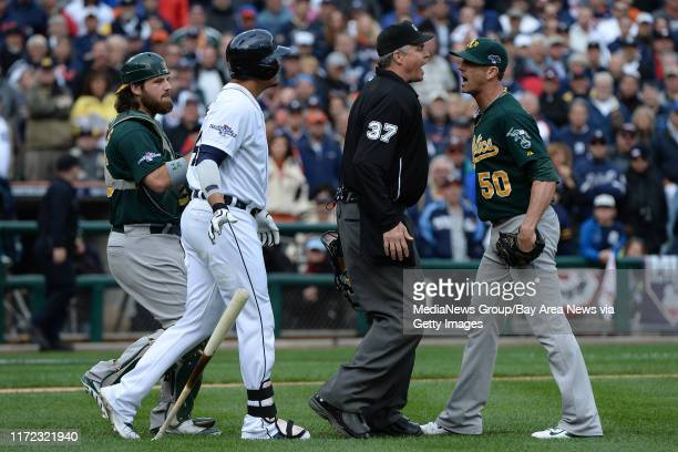 Home plate umpire Gary Darling stands between Oakland Athletics closing pitcher Grant Balfour and Detroit Tigers' Victor Martinez during a dispute in...