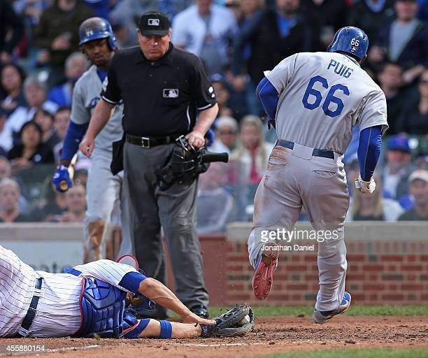 Home plate umpire Gerry Davis watches as Yasiel Puig of the Los Angeles Dodgers avoids the tag attempt by Welington Castillo of the Chicago Cubs to...