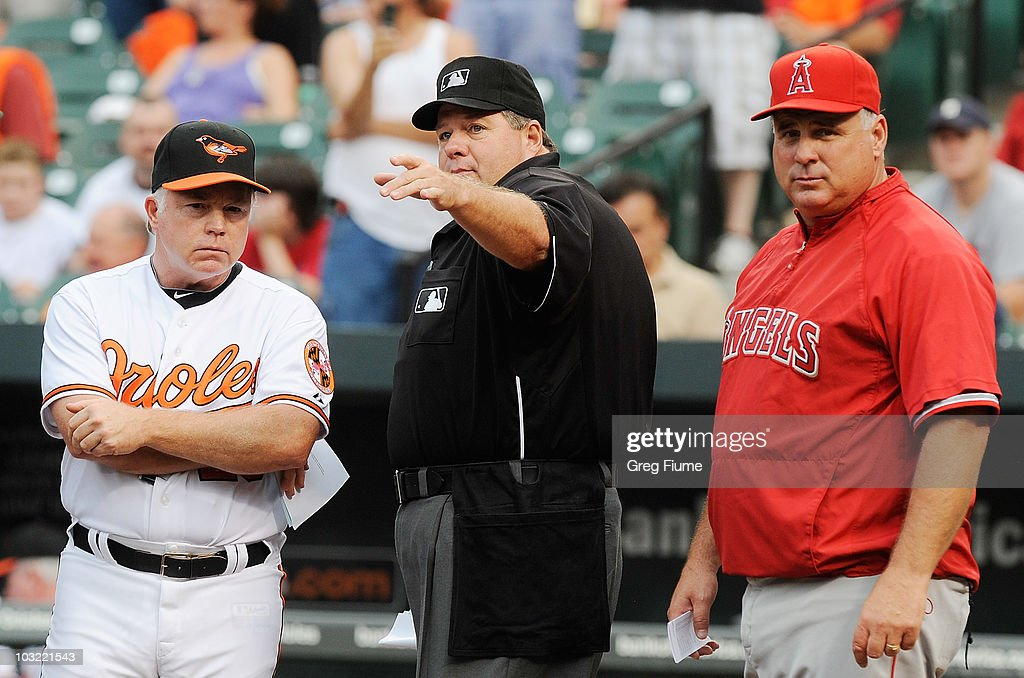 Home plate Umpire Jerry Layne talks to Manager Buck Showalter of the Baltimore Orioles and Manager Mike Scioscia of the Los Angeles Angels of Anaheim before the game at Camden Yards on August 3, 2010 in Baltimore, Maryland.