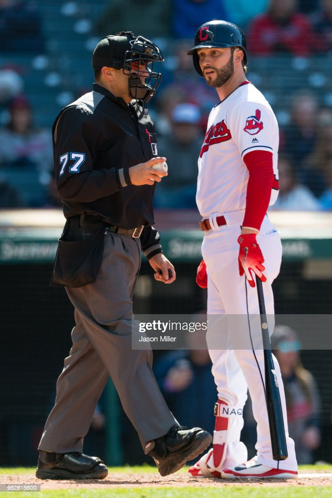 Home plate umpire Jim Reynolds #77 listens to Tyler Naquin #30 of the Cleveland Indians argue a call after Naquin struck out to end the eighth inning against the Seattle Mariners at Progressive Field on April 29, 2018 in Cleveland, Ohio. The Mariners defeated the Indians 10-4.