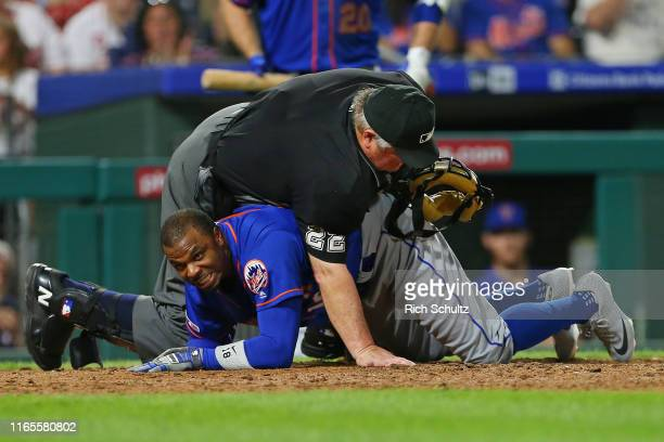Home plate umpire Joe West falls on top of Rajai Davis of the New York Mets after he was tagged out by catcher J.T. Realmuto of the Philadelphia...