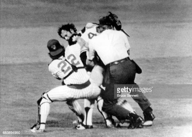 Home plate umpire John Shulock and catcher Charlie Moore of the Milwaukee Brewers try to pull Reggie Jackson of the New York Yankees off of pitcher...