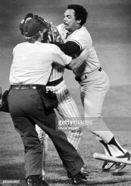Home plate umpire John Shulock tries to pull Reggie Jackson of the New York Yankees off of pitcher Mike Caldwell of the Brewers after being knocked...