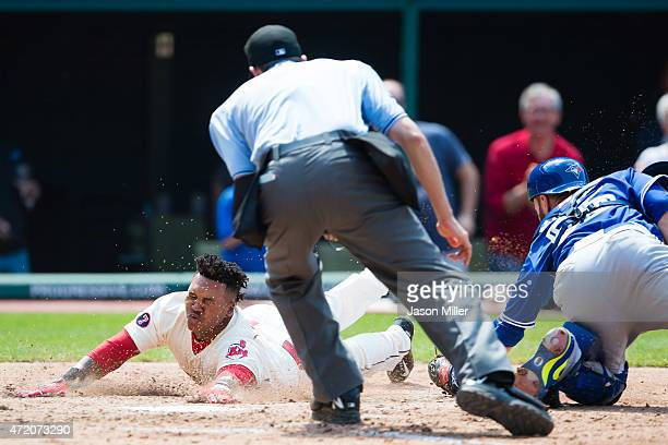 Home plate umpire John Tumpane watches as catcher Russell Martin of the Toronto Blue Jays misses the tag as Jose Ramirez of the Cleveland Indians...