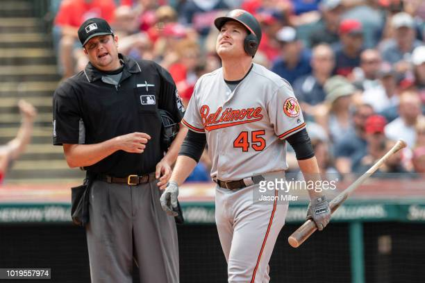 Home plate umpire Jordan Baker talks to Mark Trumbo of the Baltimore Orioles who reacts after striking out to end the top of the third inning against...