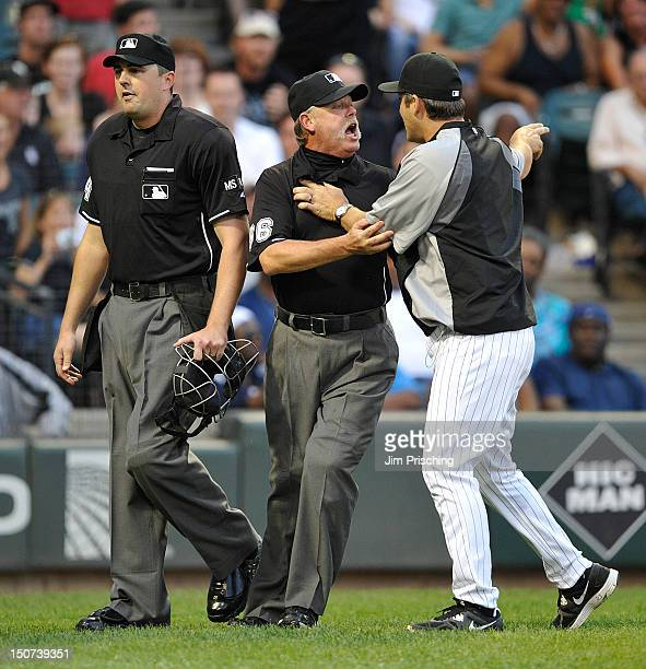 Home plate umpire Lance Barrett walks away as Umpire Jim Joyce restrains Robin Ventura of the Chicago White Sox after he was tossed out of the game...