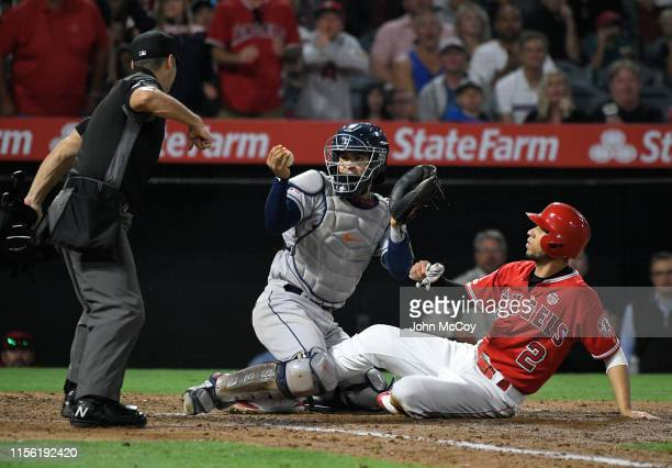 Home plate umpire Mark Wgner calls Andrelton Simmons of the Los Angeles Angels of Anaheim out at home as Robinson Chirinos of the Houston Astros...