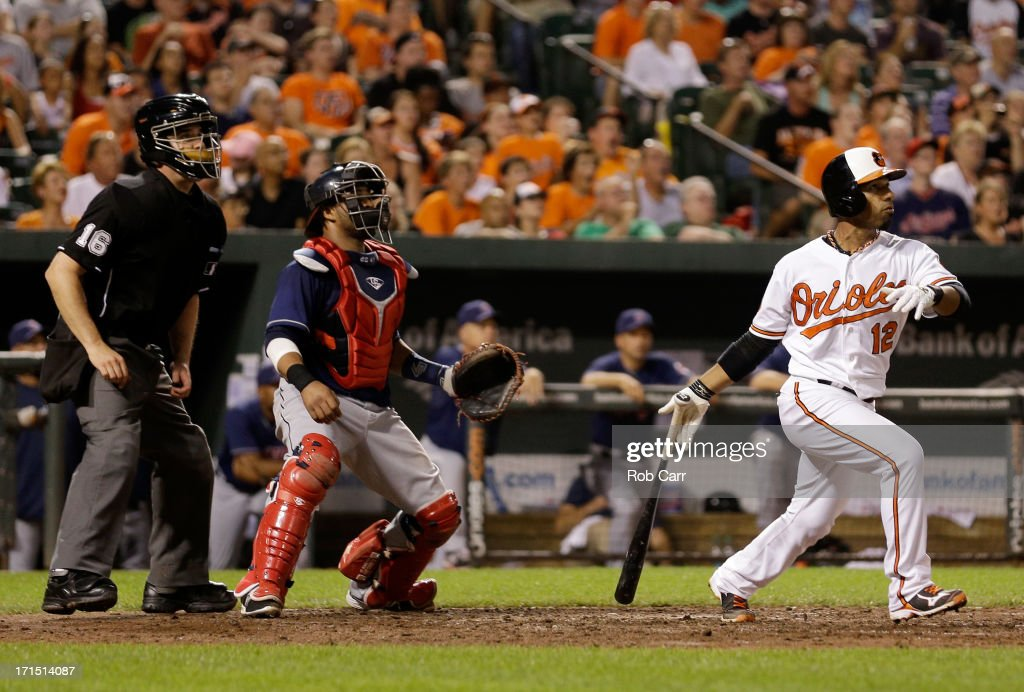 Home plate umpire Mike DiMuro and catcher Carlos Santana #41 of the Cleveland Indians look on as Alexi Casilla #12 of the Baltimore Orioles follows his three RBI home run in the seventh inning of the Orioles 6-3 win at Oriole Park at Camden Yards on June 25, 2013 in Baltimore, Maryland.