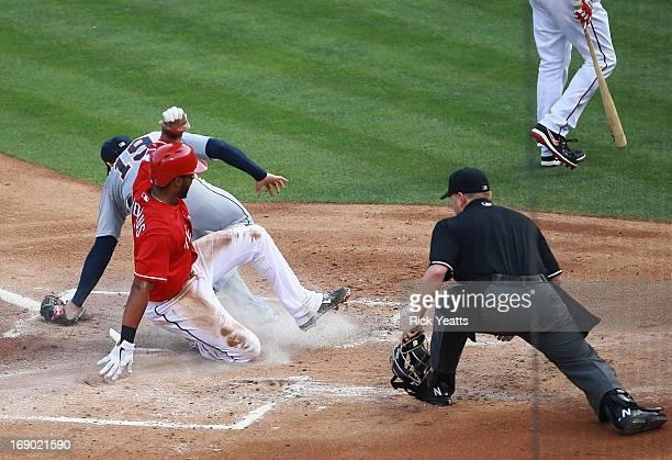 Home plate umpire Mike Muchlinski looks on as Elvis Andrus of the Texas Rangers beats the throw to score against Anibal Sanchez of the Detroit Tigers...