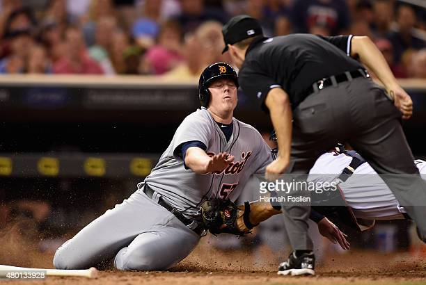 Home plate umpire Mike Winters looks on as Kurt Suzuki of the Minnesota Twins tags out Marc Krauss of the Detroit Tigers during the eighth inning of...