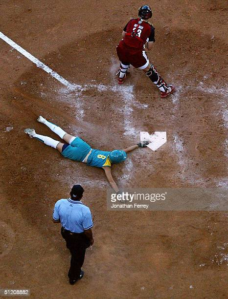 Home plate umpire Santos Vasquez watches as Sandra Allen of Australia scores her team's only run as catcher Stacey Nuveman of the United States cuts...