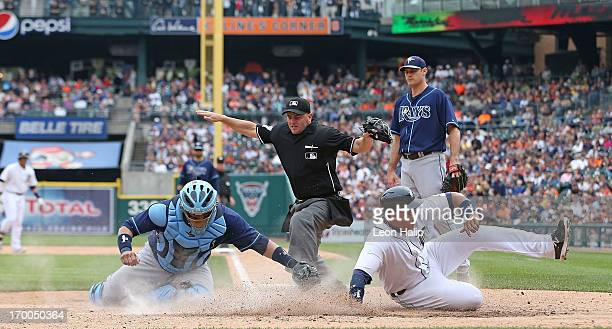 Home plate umpire Scott Barry calls Miguel Cabrera of the Detroit Tigers safe at home as Jose Molina of the Tampa Bay Rays attempts to make the tag...