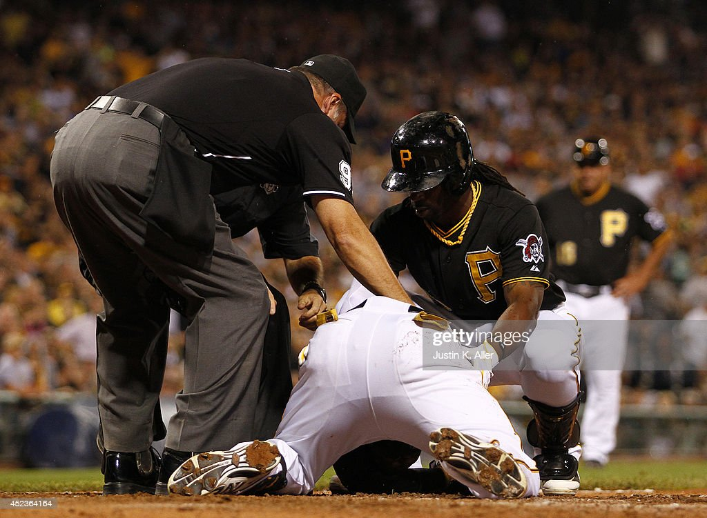 Home plate umpire Tim Timmons and Andrew McCutchen #22 check on Starling Marte #6 of the Pittsburgh Pirates after being hit in the head with a pitch in the seventh inning against the Colorado Rockies during the game at PNC Park July 18, 2014 in Pittsburgh, Pennsylvania.