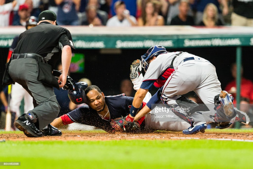 Home plate umpire Todd Tichenor #13 watches as Edwin Encarnacion #10 of the Cleveland Indians is tagged out at home plate by catcher Jason Castro #21 of the Minnesota Twins during the third inning at Progressive Field on September 26, 2017 in Cleveland, Ohio.