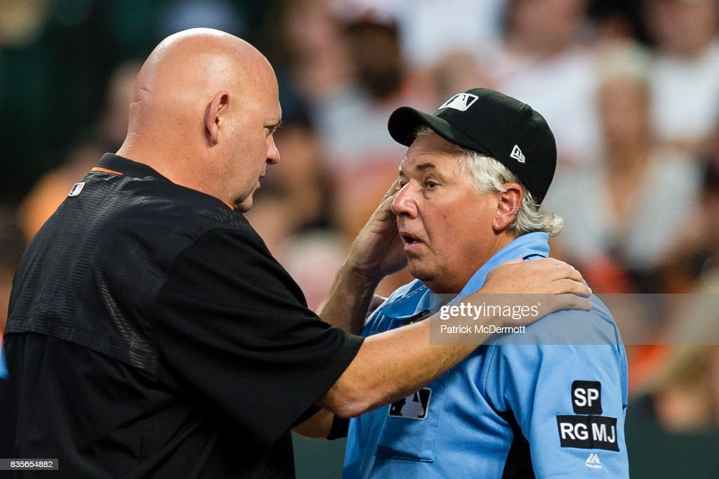 Home plate umpire Tom Hallion #20 is attended to by Baltimore Orioles assistant athletic trainer Brian Ebel after being hit by a ball in the second inning during a game between the Los Angeles Angels of Anaheim and Baltimore Orioles at Oriole Park at Camden Yards on August 19, 2017 in Baltimore, Maryland.