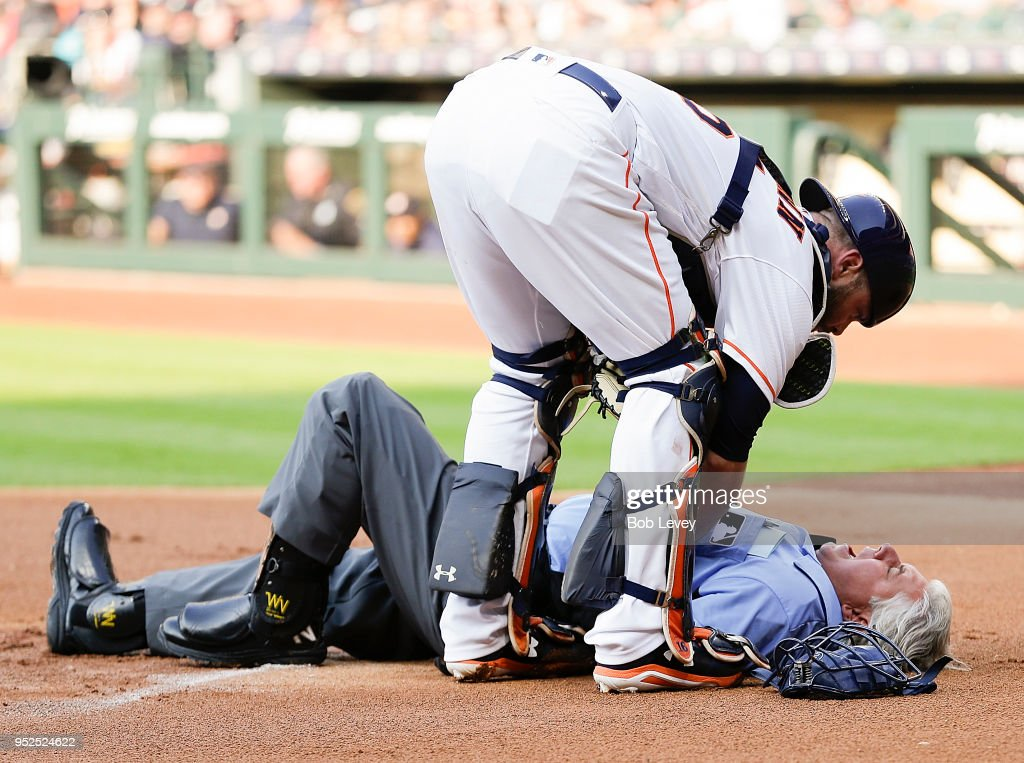 Home plate umpire Tom Hallion #20 is checked on by Brian McCann #16 of the Houston Astros after he was hit by a ball in the first inning at Minute Maid Park on April 28, 2018 in Houston, Texas.