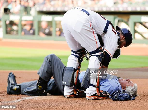 Home plate umpire Tom Hallion is checked on by Brian McCann of the Houston Astros after he was hit by a ball in the first inning at Minute Maid Park...
