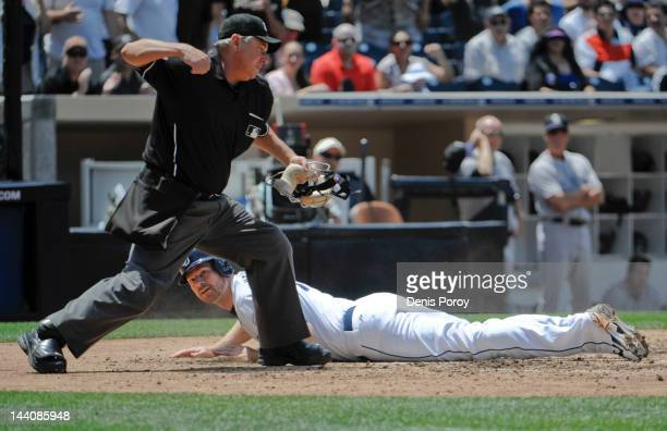 Home plate umpire Tom Hallion makes the call after Chase Headley of the San Diego Padres was tagged out while trying to score during the third inning...