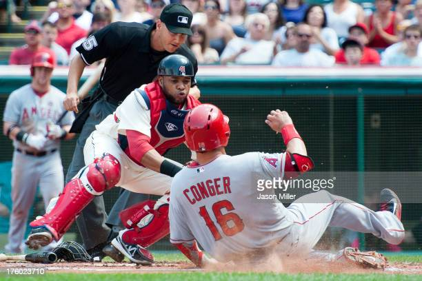 Home plate umpire Vic Carapazza watches as catcher Carlos Santana of the Cleveland Indians tags out Hank Conger of the Los Angeles Angels of Anaheim...