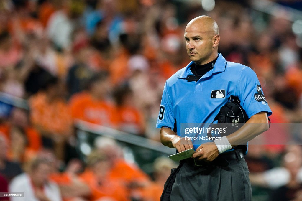 Home plate umpire Vic Carapazza #19 wears a white wristband in the sixth inning during a game between the Los Angeles Angels of Anaheim and Baltimore Orioles at Oriole Park at Camden Yards on August 19, 2017 in Baltimore, Maryland.