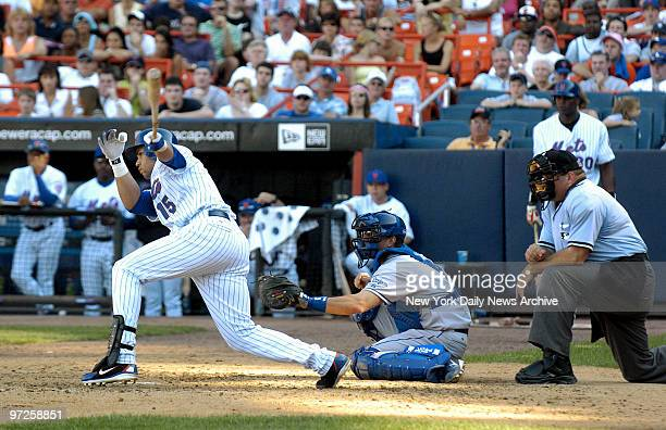 Home plate umpire Wally Bell and Los Angeles Dodgers' catcher Jason Phillips look on as New York Mets' Carlos Beltran hits a one-run single to center...