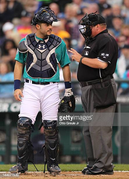 Home plate umpire Wally Bell signals that there are two outs after catcher Jesus Montero of the Seattle Mariners mistakenly headed to the dugout...