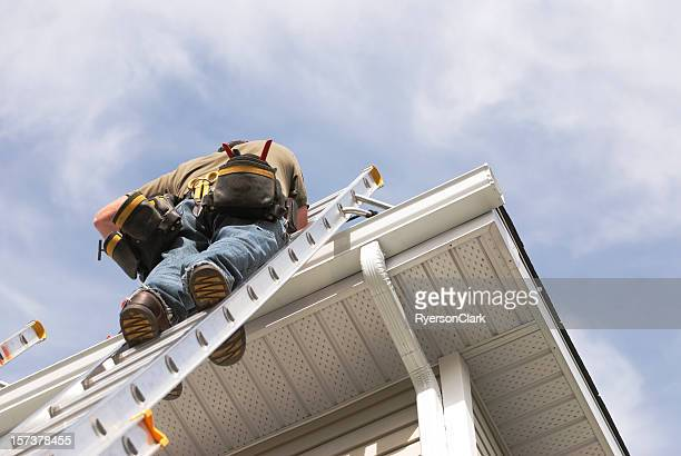 home repairs handyman up a ladder outdoors - roof stock photos and pictures