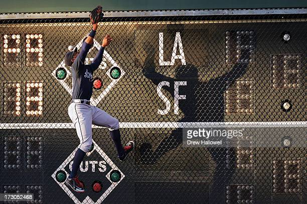 A home run ball hit by Humberto Quintero of the Philadelphia Phillies goes past the head of Jason Heyward of the Atlanta Braves as he jumps to make...