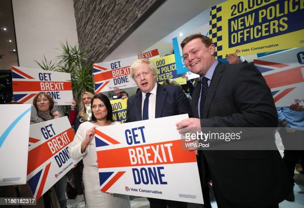 Home Secretary Priti Patel, Prime Minister Boris Johnson and MP Will Quince hold a sign at a campaign rally event on December 2, 2019 in Colchester,...