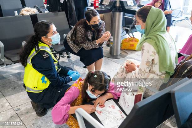 Home Secretary Priti Patel talking to Malalai Hussiny a refugee from Afghanistan who arrived on a evacuation flight at Heathrow Airport on August 26,...