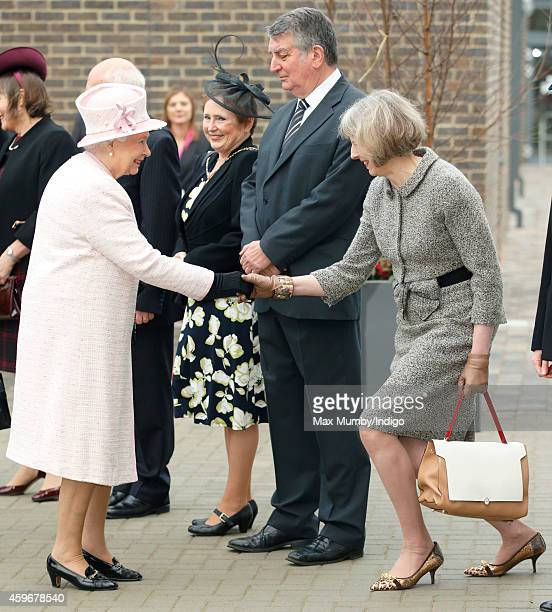 Home Secretary Theresa May curtseys to Queen Elizabeth II as she visits Holyport College on November 28 2014 in Holyport England